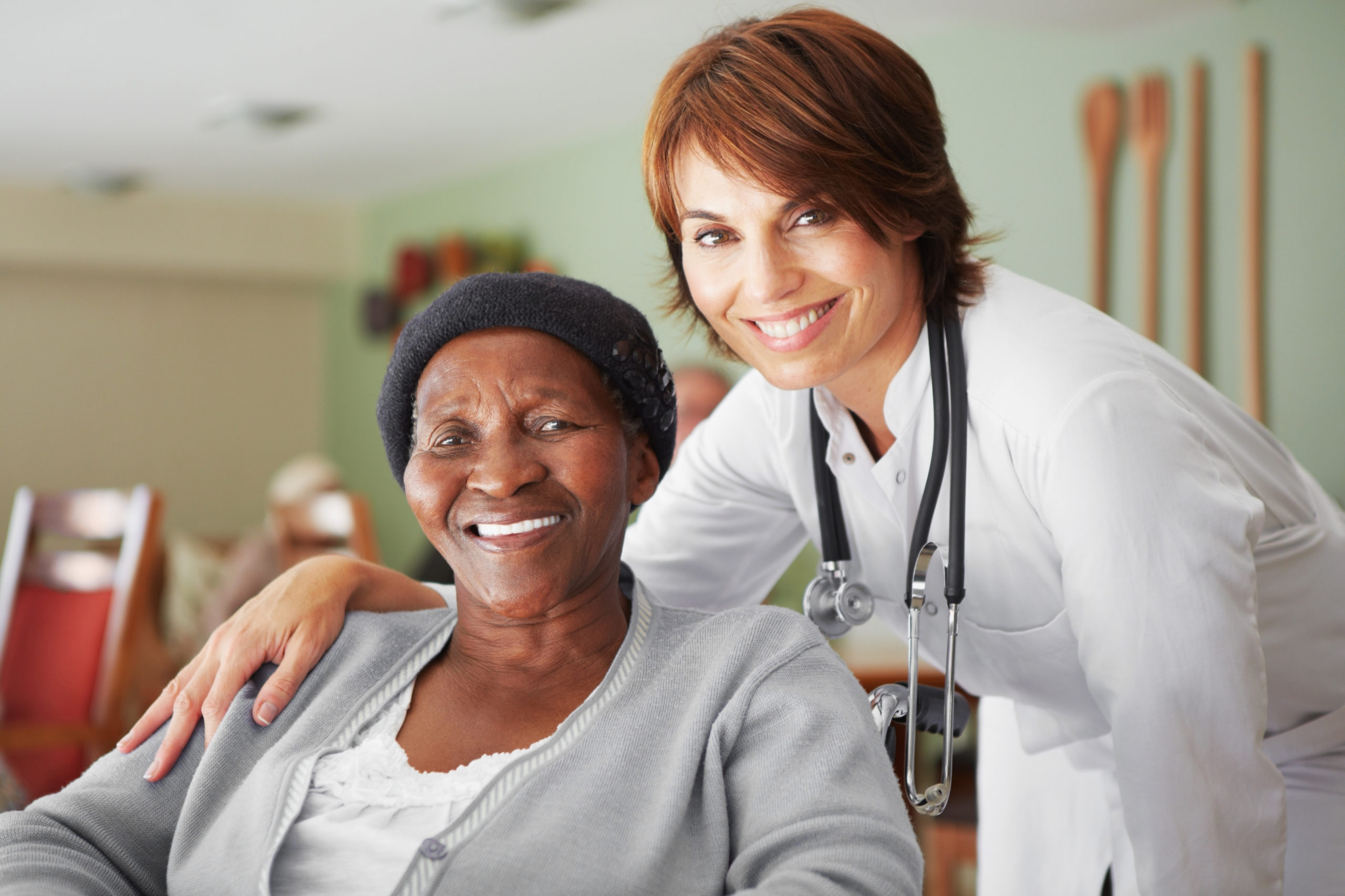 A supportive female doctor alongside an elderly african patient in a retirement home