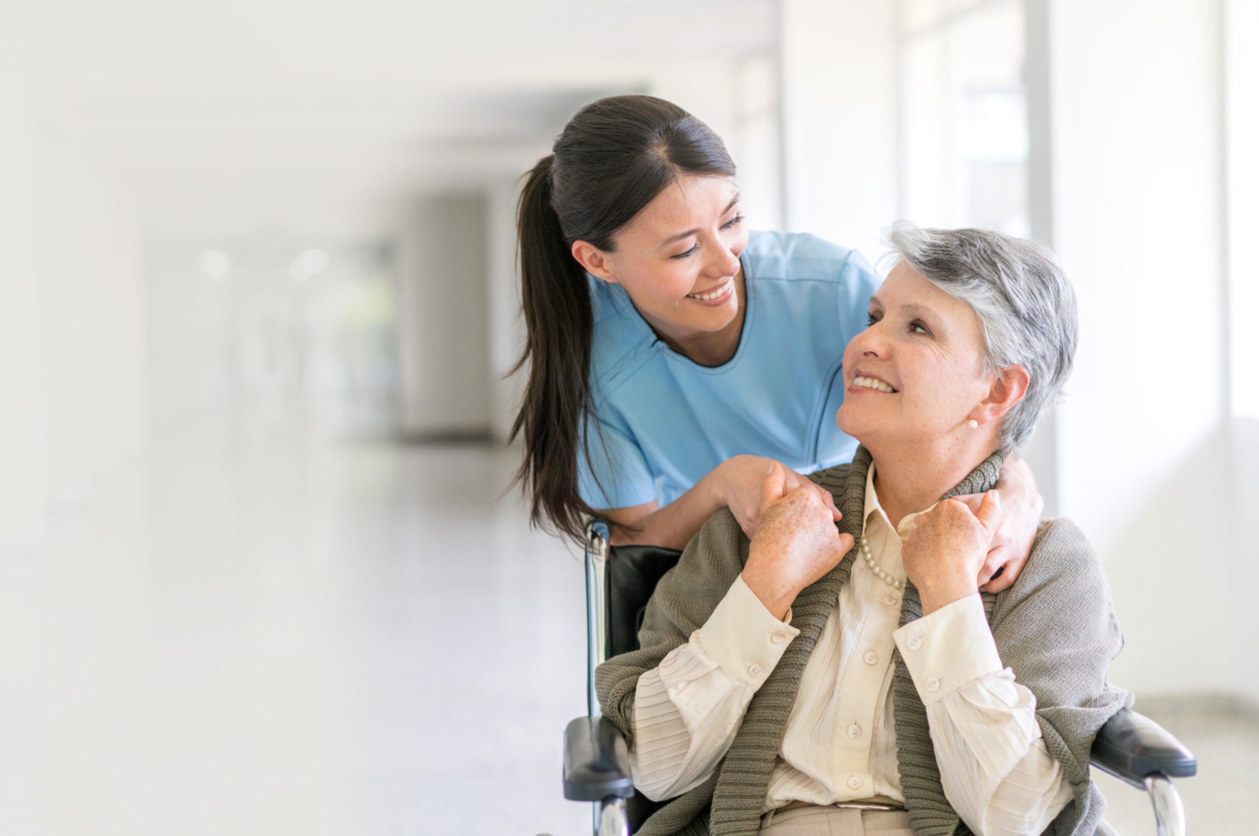 Handicap patient in a wheelchair at the hospital talking to a friendly nurse and looking very happy - healthcare and medicine concepts