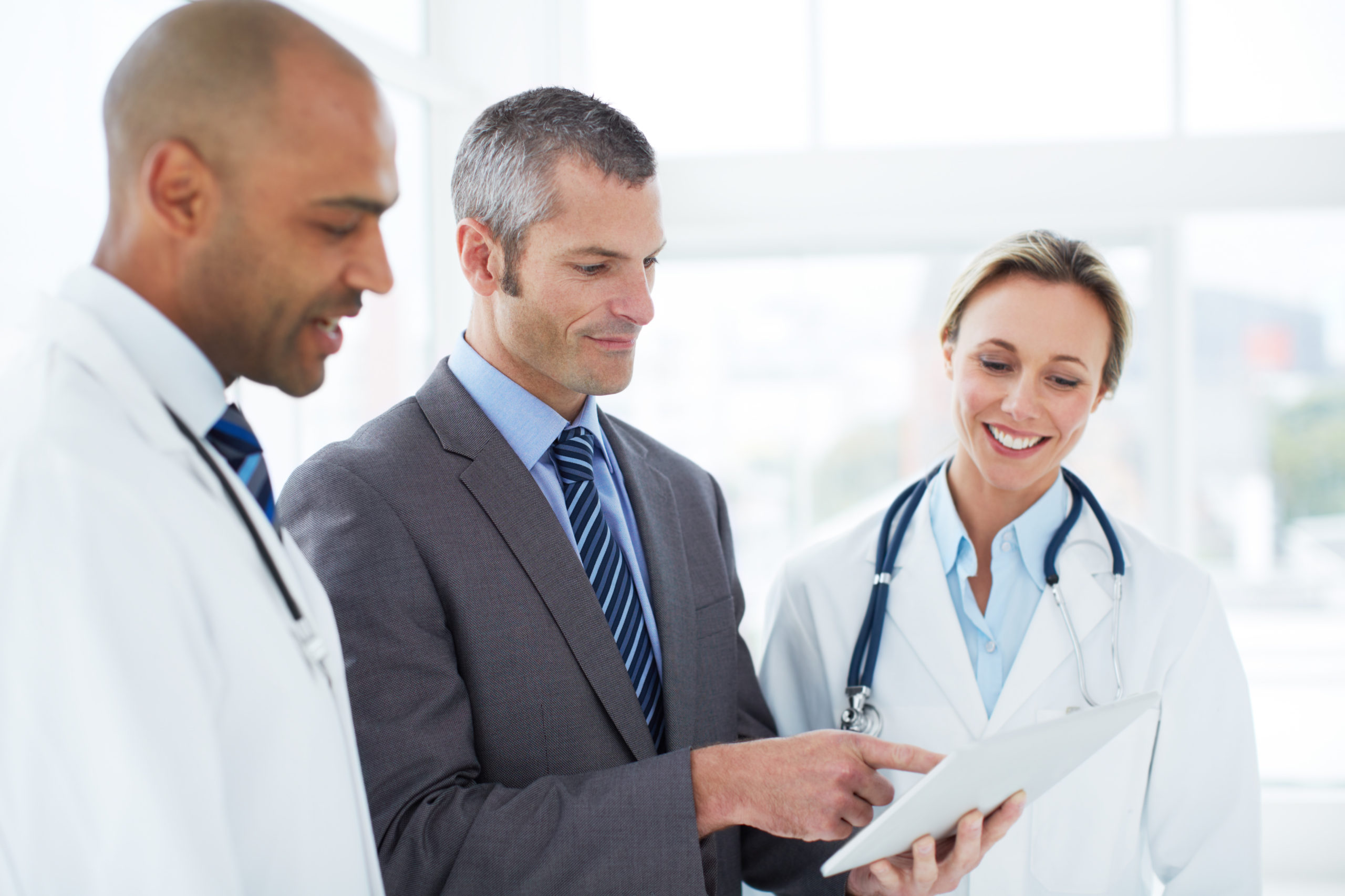 Doctors discussing a tablet with a hospital administrator
