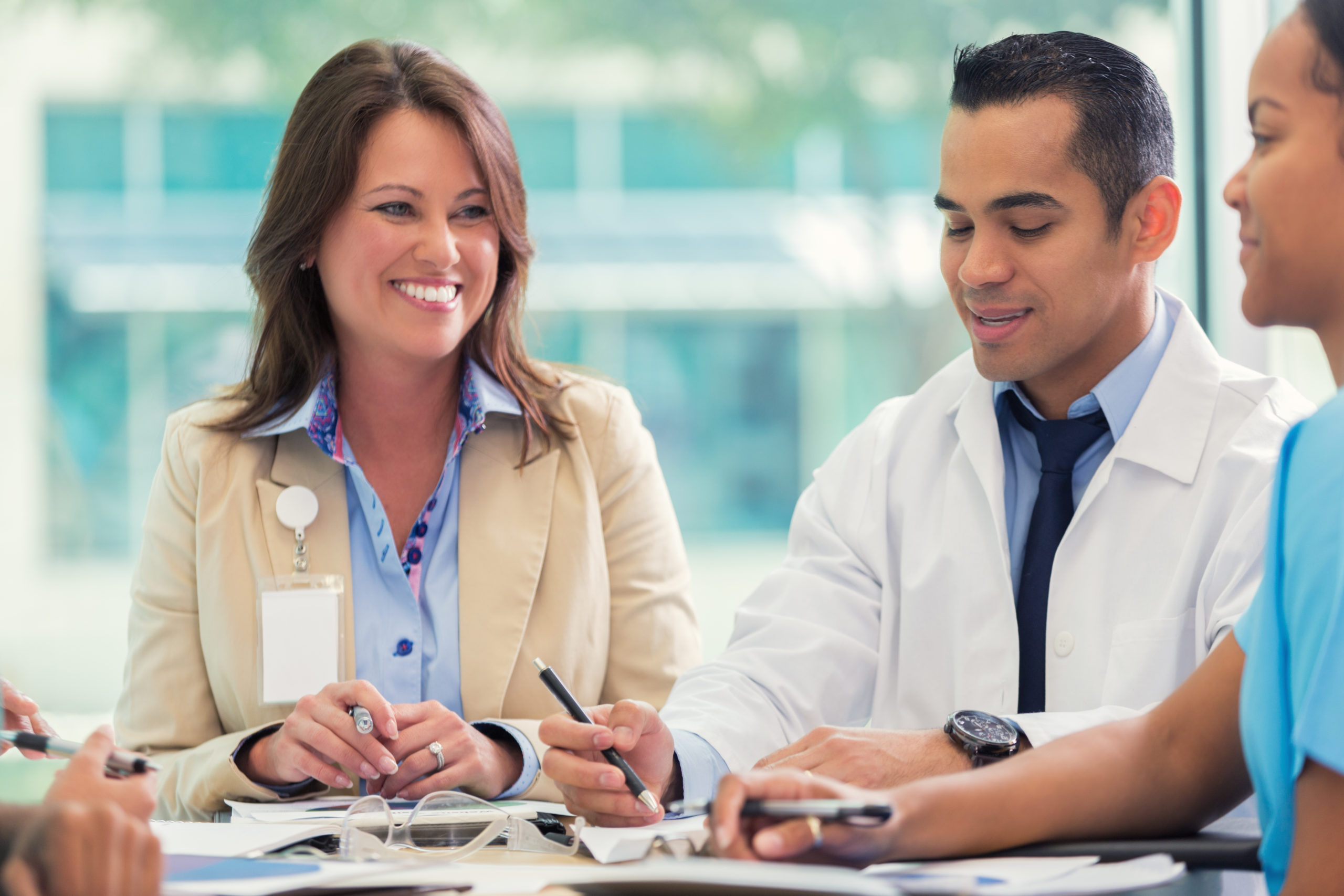 Mid adult Hispanic doctor and mid adult Caucasian female hospital administrator discuss hospital policy and procedures during staff meeting.