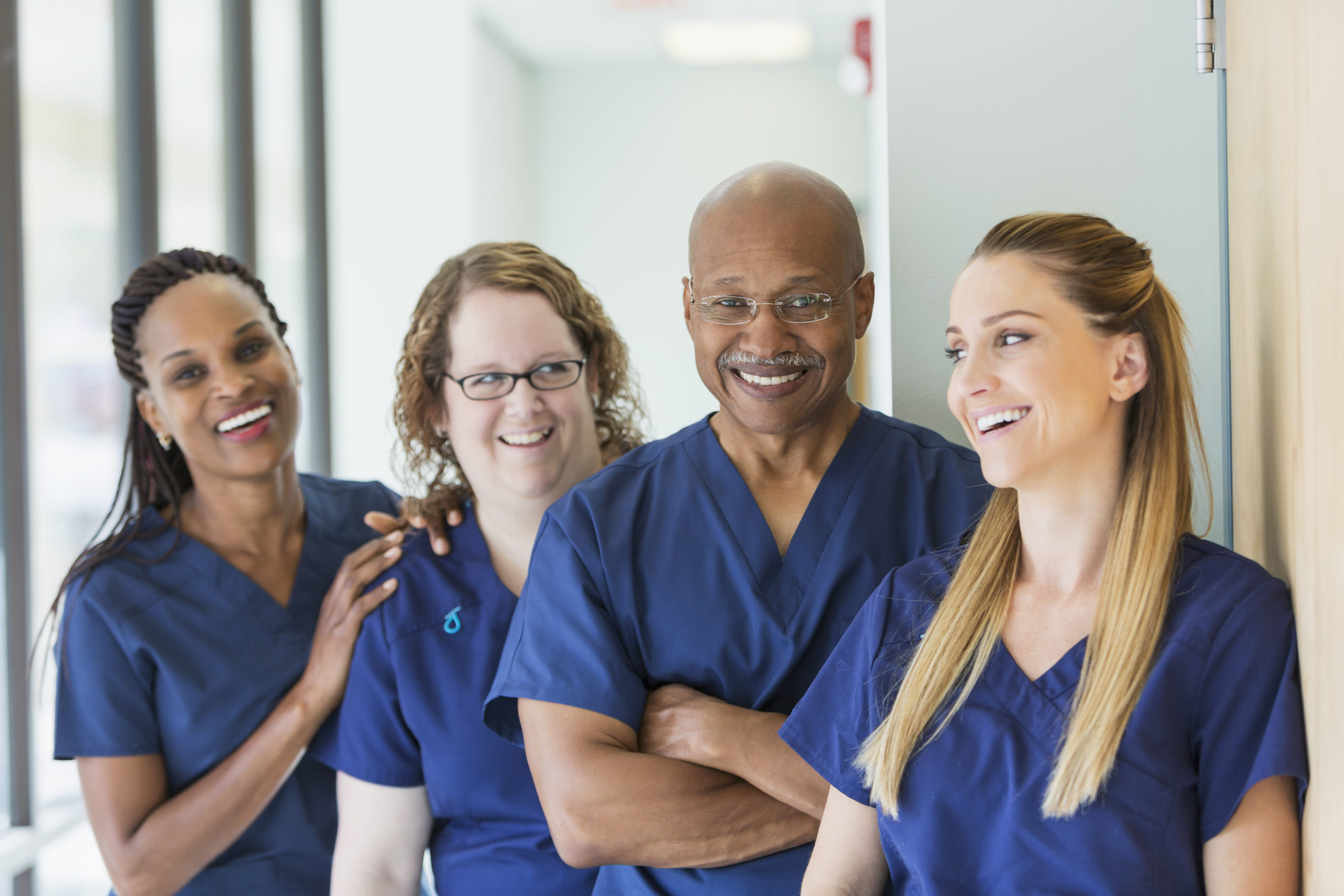 A team of four multi-ethnic medical professionals standing in a corridor, wearing blue scrubs. The focus is on the African-American senior man, in his 60s smiling at the camera.