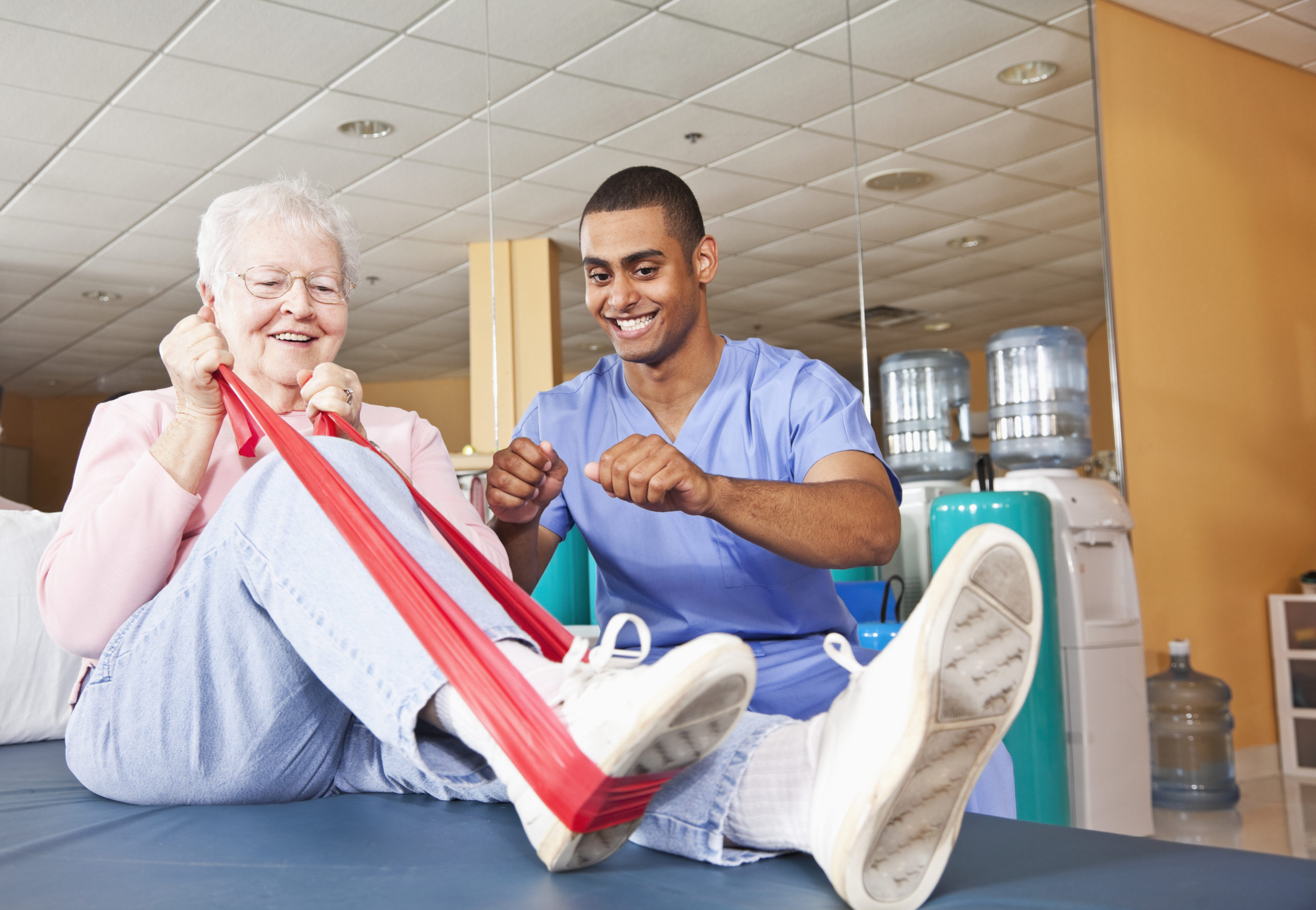 Physical therapist helping senior woman (80s) with leg exercises.